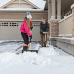 Kids shoveling snow off driveway
